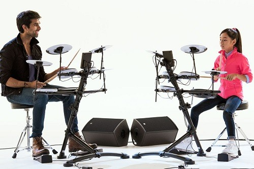 Man And Young Girl Drumming On Electric Drums